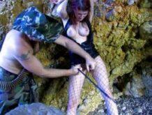 Fetischsex mit einer rothaarigen Sklavin in einer Höhle